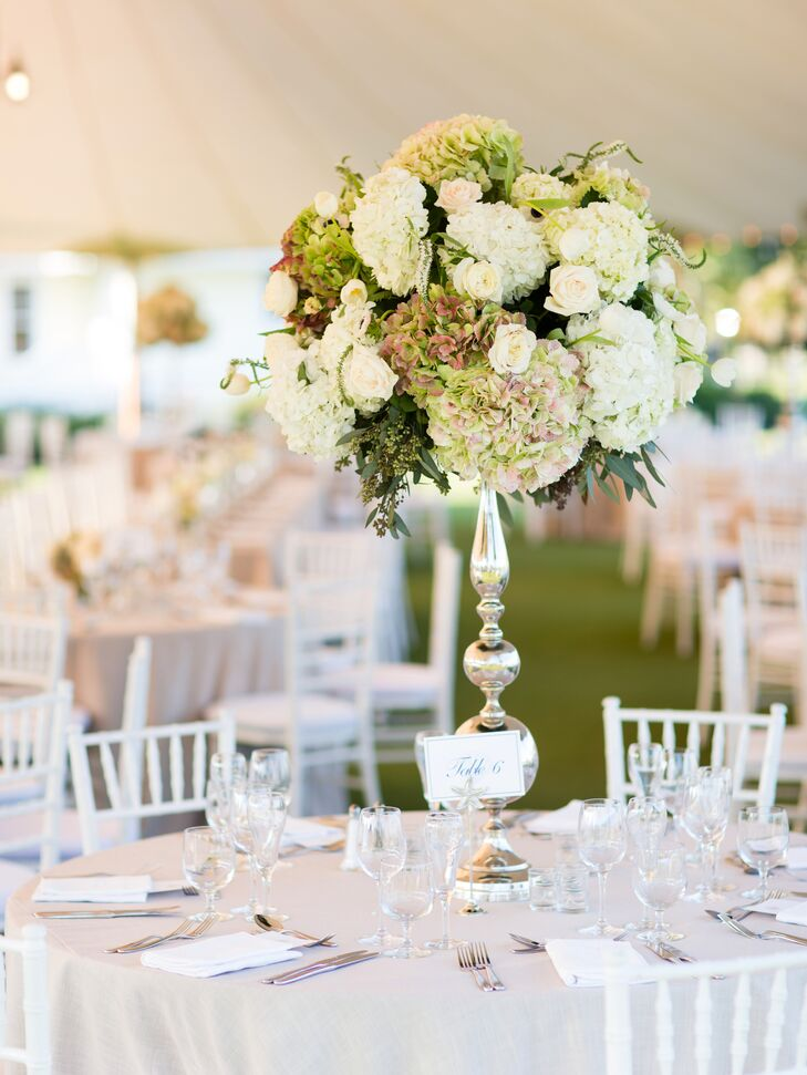 Tall glass candelabra vases held lush arrangements of white and green hydrangeas for the round table centerpiece decor.