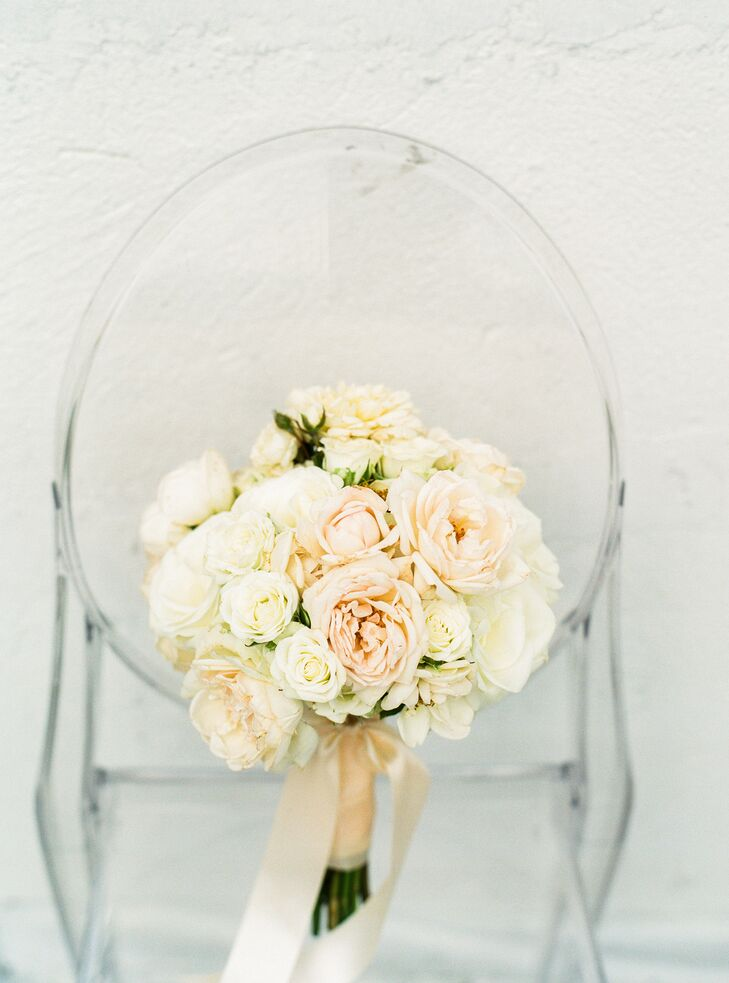 For their flowers, Mia and Jake kept things simple, opting for classic arrangements of hydrangeas, carnations and roses. For the bridal bouquet, Celadon and Celery Events created a romantic bundle of ivory and blush roses, which they accented with blush satin ribbon for a refined, ladylike finish.