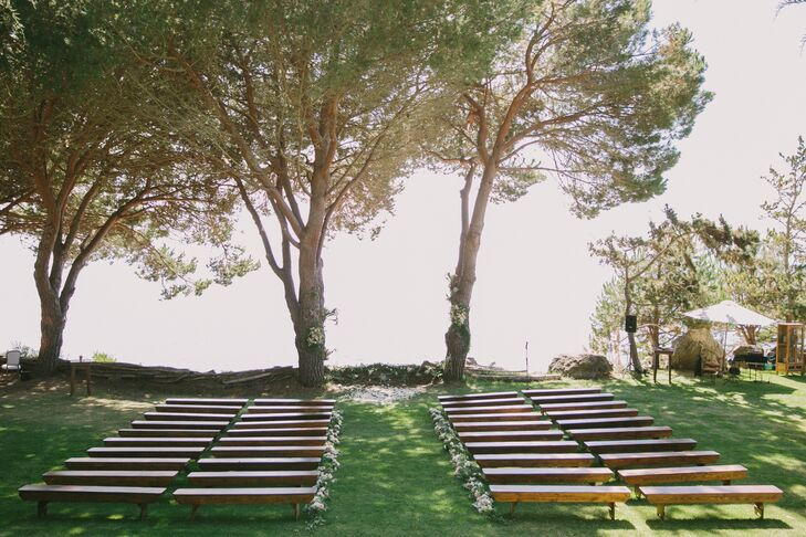 Rory and Kevin's 120 guests sat on wooden benches to watch them exchange vows on a cliff under an arch of pine trees overlooking the Pacific Ocean.