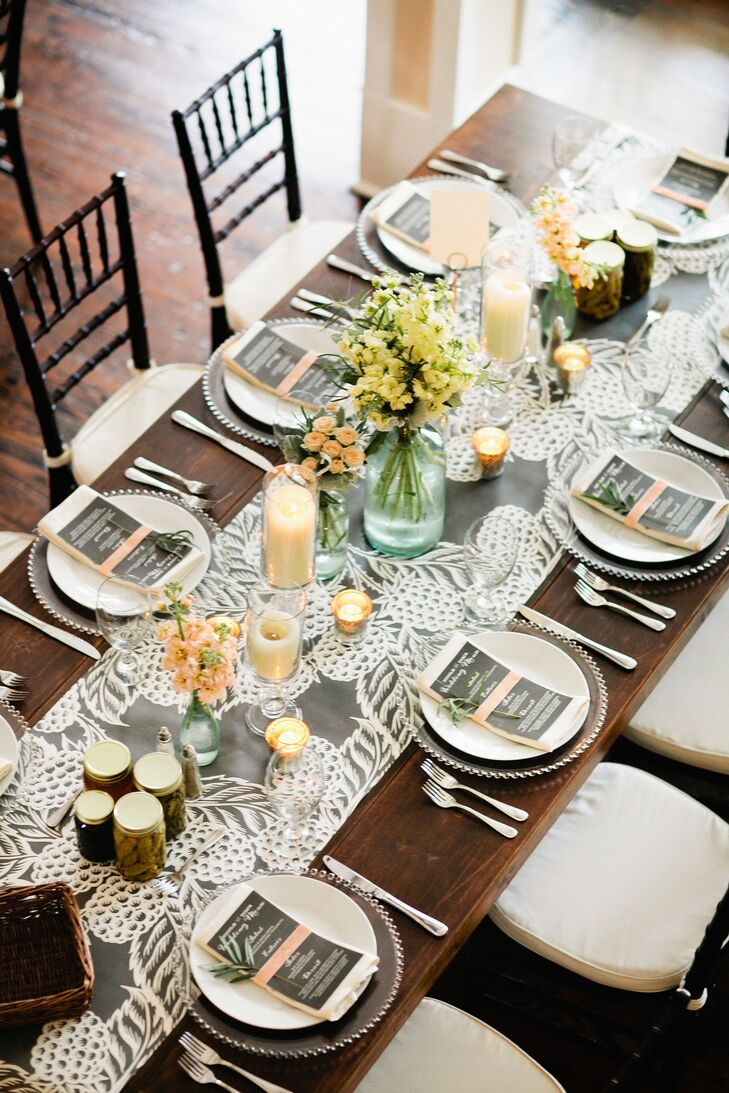 The reception tables were topped with gray and white linen table runners that added a little elegance to the wooden tables. They were topped with roses, stock and dusty miller in glass vases, along with pillar candles for an extra pop of color and romance.