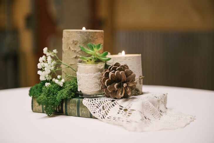 Pinecones, birch wood votives and lace doilies came together to create a centerpiece stack, finished with vintage hardcover books sourced by Taylor's librarian aunt.