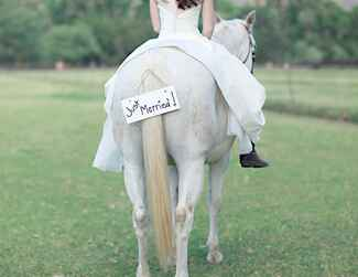 Bride riding a horse with just married sign
