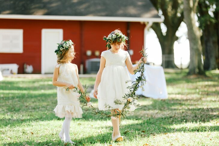 Sarah and Charles had two flower girls at their wedding. One wore a dress from Target and the other's grandmother made hers. Both wore lily-of-the-valley flower crowns. Instead of scattering petals or something else, they carried a garland made of olive branch and blush-colored ranunculus.