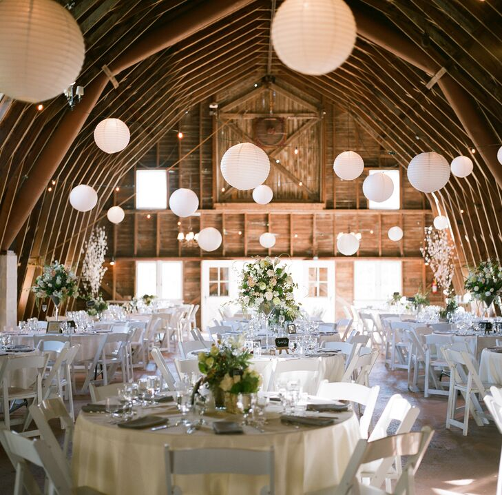 The natural beauty of the barn's wooden arches served as the main focal point of the rustic reception. To highlight the beams, white paper lanterns were strung high above the barn to naturally draw guest's eyes upward.
