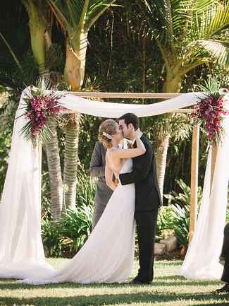Draped white fabric arch with berry-colored flowers