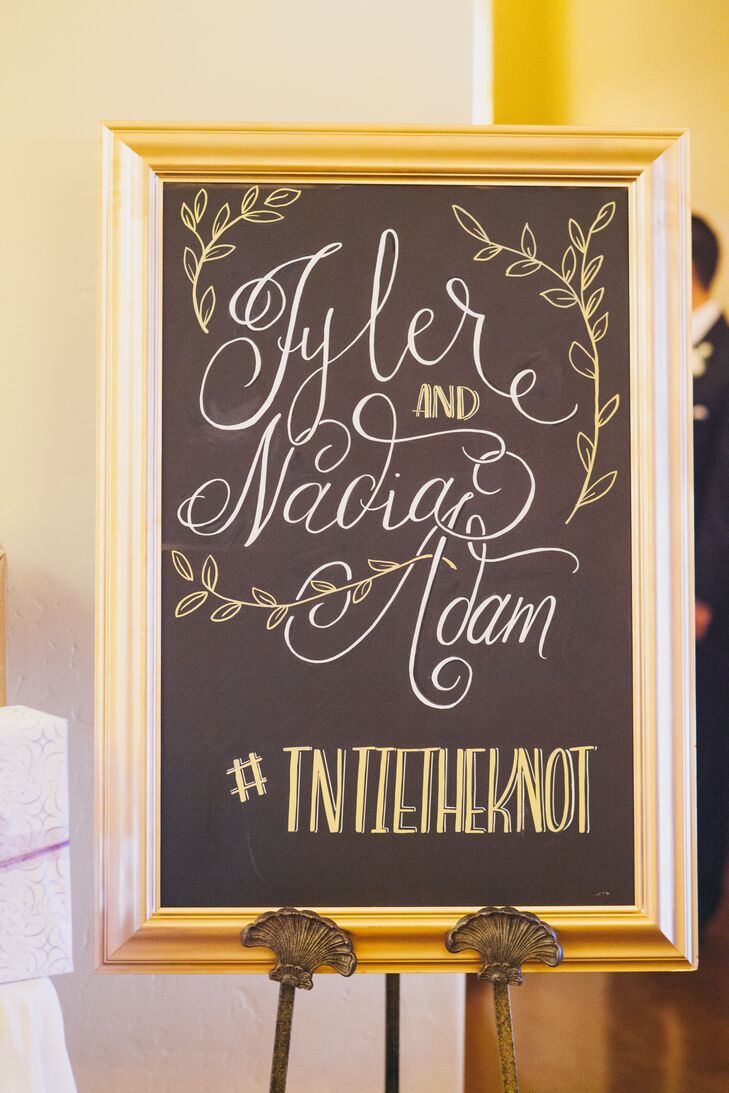 "A gold glamorous frame bordered a black chalkboard sign that read ""Tyler and Nadia Adam"" with sketches of leaves surrounding the text. Their hashtag, written at the bottom, encouraged guests show off the wedding over social media throughout the day."