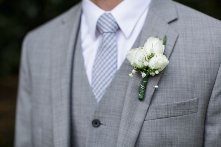 Dylan wore a three-piece gray suit for their romantic wedding at Mountain Magnolia Inn, Suites and Restaurant in Hot Springs, North Carolina. He completed his look with a checkered tie and white rose and baby's breath boutonniere.