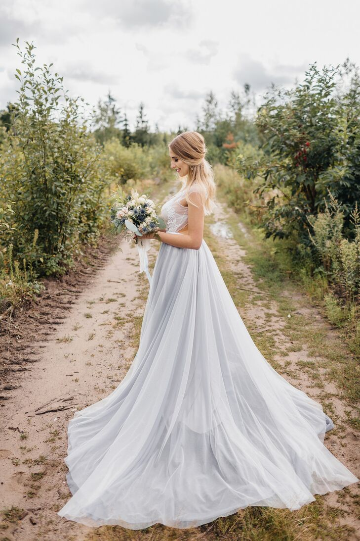 """I fell in love with the wedding dresses of one Belarusian brand even before I started preparations for my wedding,"" Katya says. ""They stood out by their originality, grace and fantastic colors."" On her wedding day, Katya donned an A-line gown with an ivory pearl-embellished top and a blue tulle skirt."