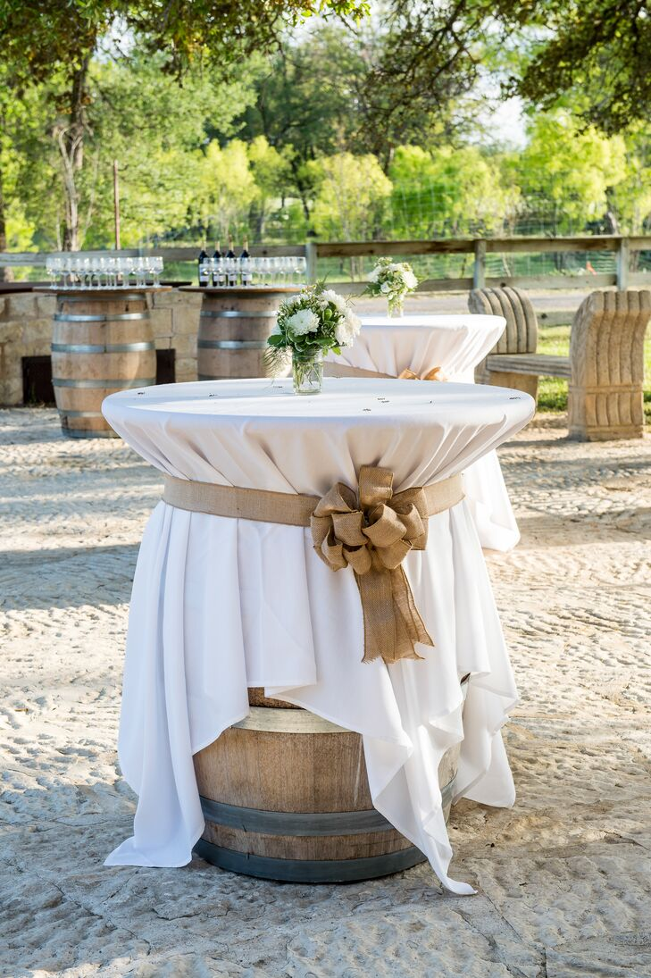 Cocktail-hour tables were rustic wooden wine barrels topped with white tablecloths and fastened with oversize burlap bows. White chrysanthemums with leafy greens completed the effortless style.