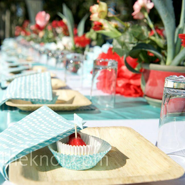 Blue agave, red carnations and colorful paper pom poms combined with bamboo plates and mod napkins for a festive, garden-style tablescape.
