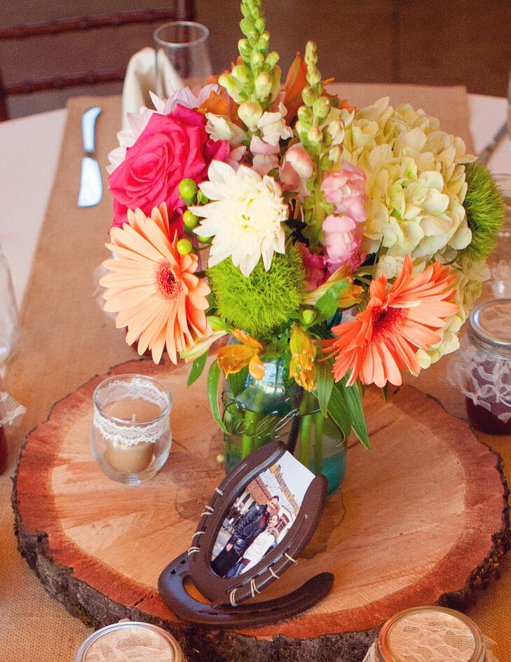 A flower arrangement of orange and white daisies, coral roses, green hydrangeas and other green details was positioned on a slab of wood, surrounded by jars of jam that were given to guests as wedding favors.