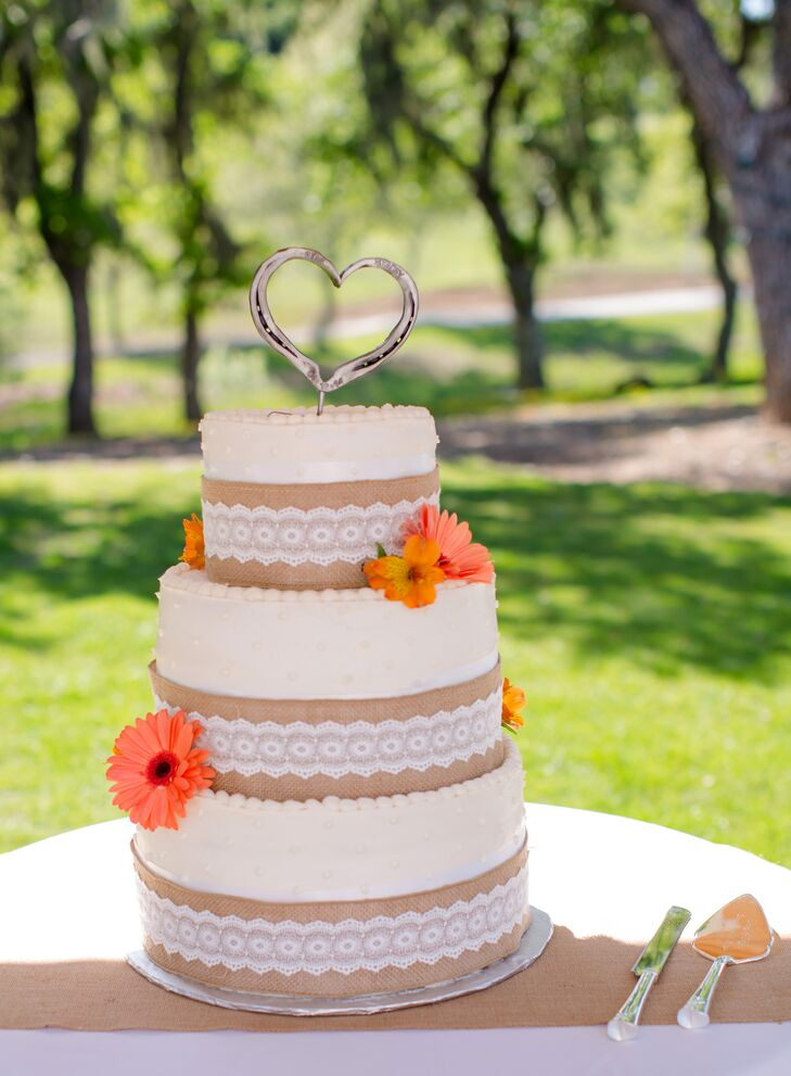 Cakes by Judy created a three-tiered ivory wedding cake for the celebration, accented with orange daisies and had a heart shaped cake topper.