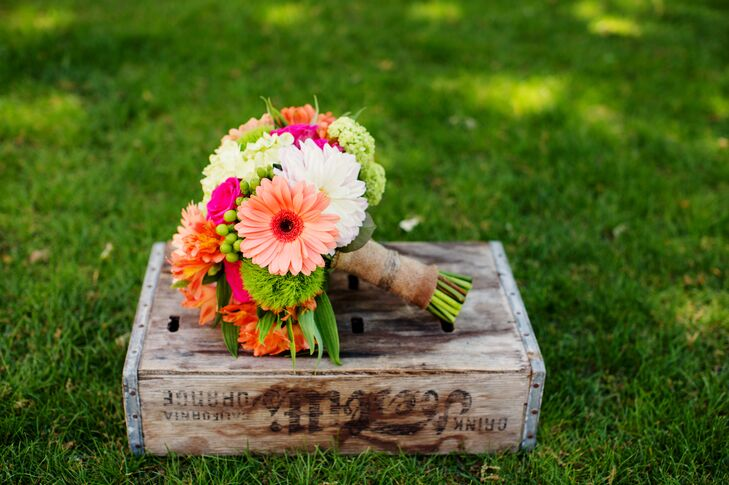 The bridal bouquet had orange and white daisies, coral roses and hydrangeas accents with other green details and was designed by Lori Boe Floral Design.