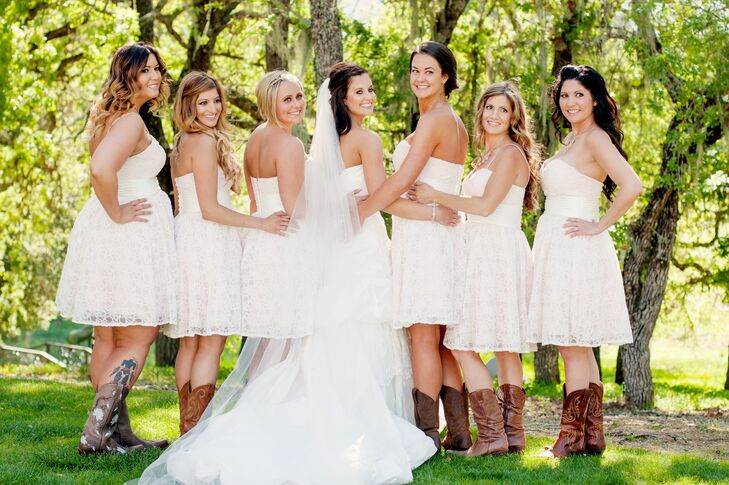 The bride stood with her bridesmaids, who wore short white strapless dresses and brown cowboy boots that added to the country theme.