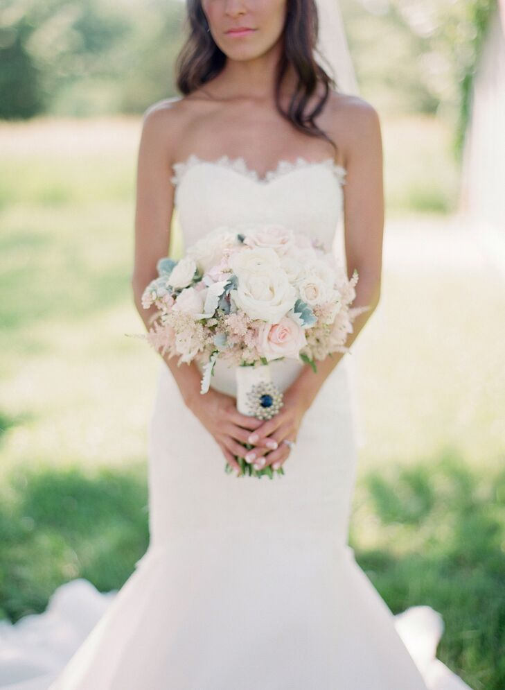 Andrea carried a textured hand-tied bouquet of pale pink peonies, champagne spray roses, ivory garden roses, white and pale pink ranunculus, pale peach and pink stock, dusty miller and blush astilbes. Andrea complemented her bouquet with a royal blue crystal broach, which she pinned to the stems.