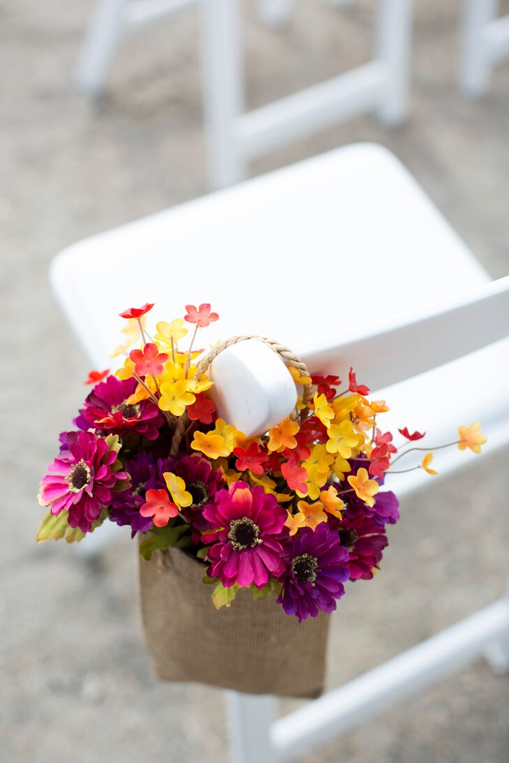 To introduce a splash of color to the mountain top ceremony space, Gabrielle and Joe dressed up the aisle with bright, rustic arrangements of Gerbera daisies and small fabric flowers in seasonal colors.