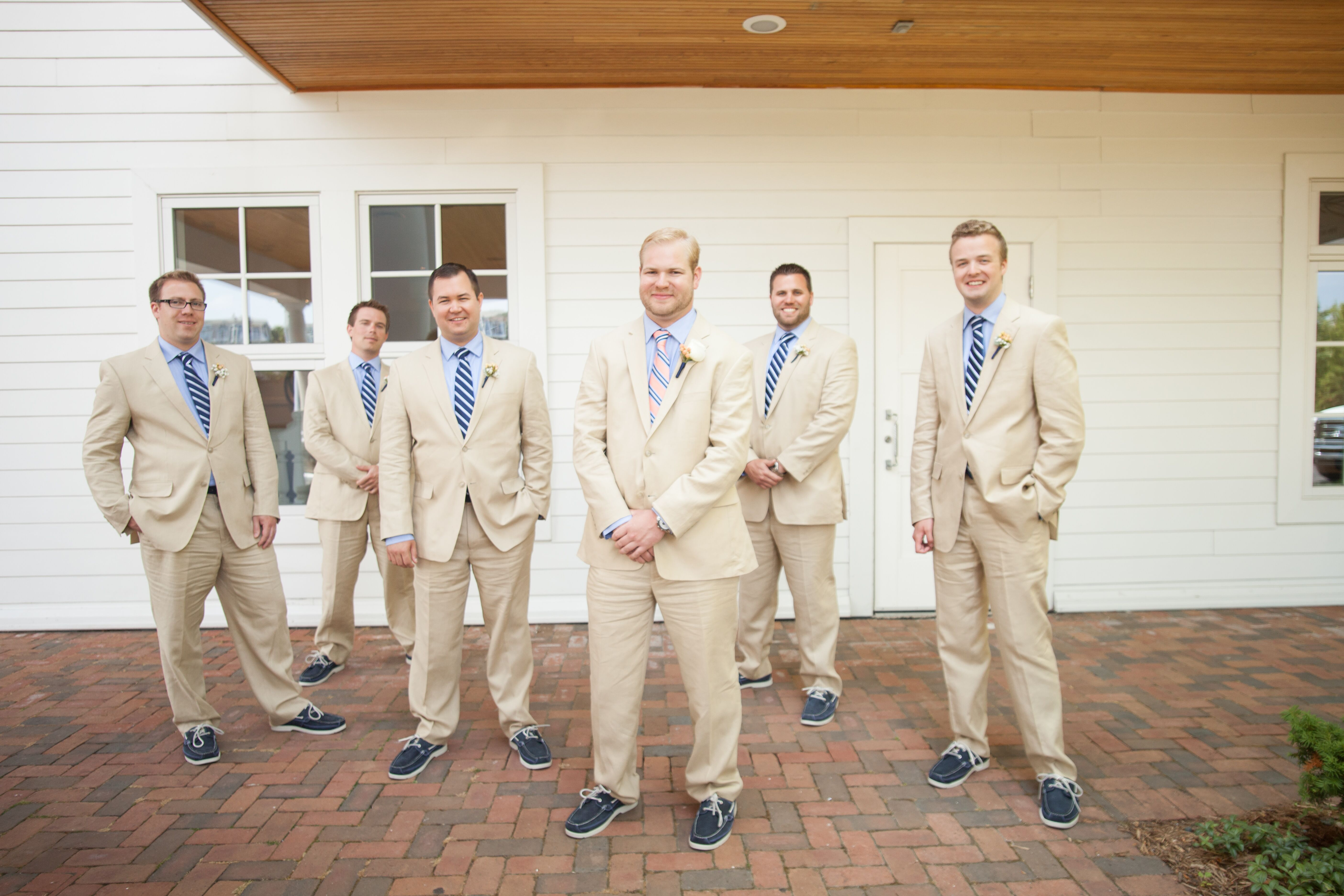 groomsmen in tan suits with striped navy ties and boat shoes