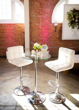 White cushioned high chairs and glass table
