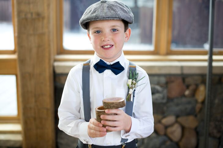 For a newsboy-inspired look, the ring bearer wore a classic gray flat cap, gray suspender s and a navy diamond-shaped bow tie.