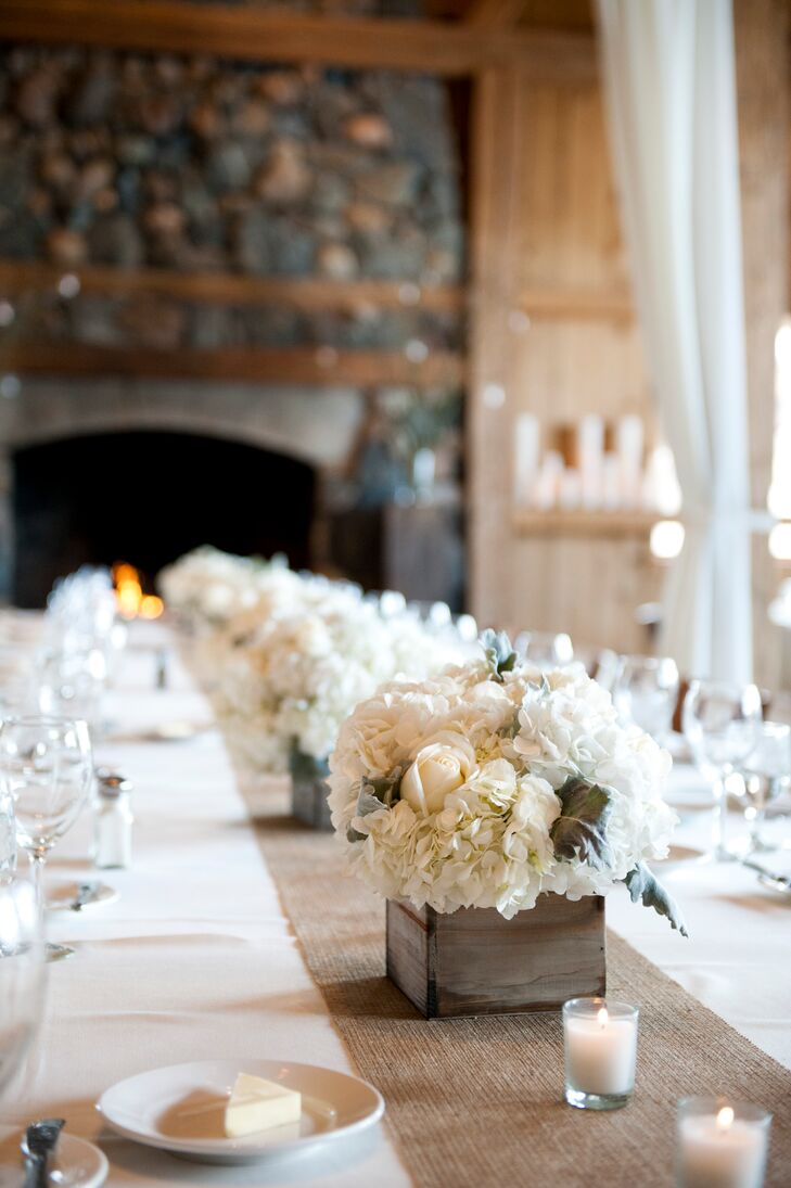 Each of the reception tables featured a different type of floral arrangement. The long reception tables were lined with cool ivory rose and hydrangea centerpieces arranged in rustic wooden boxes.