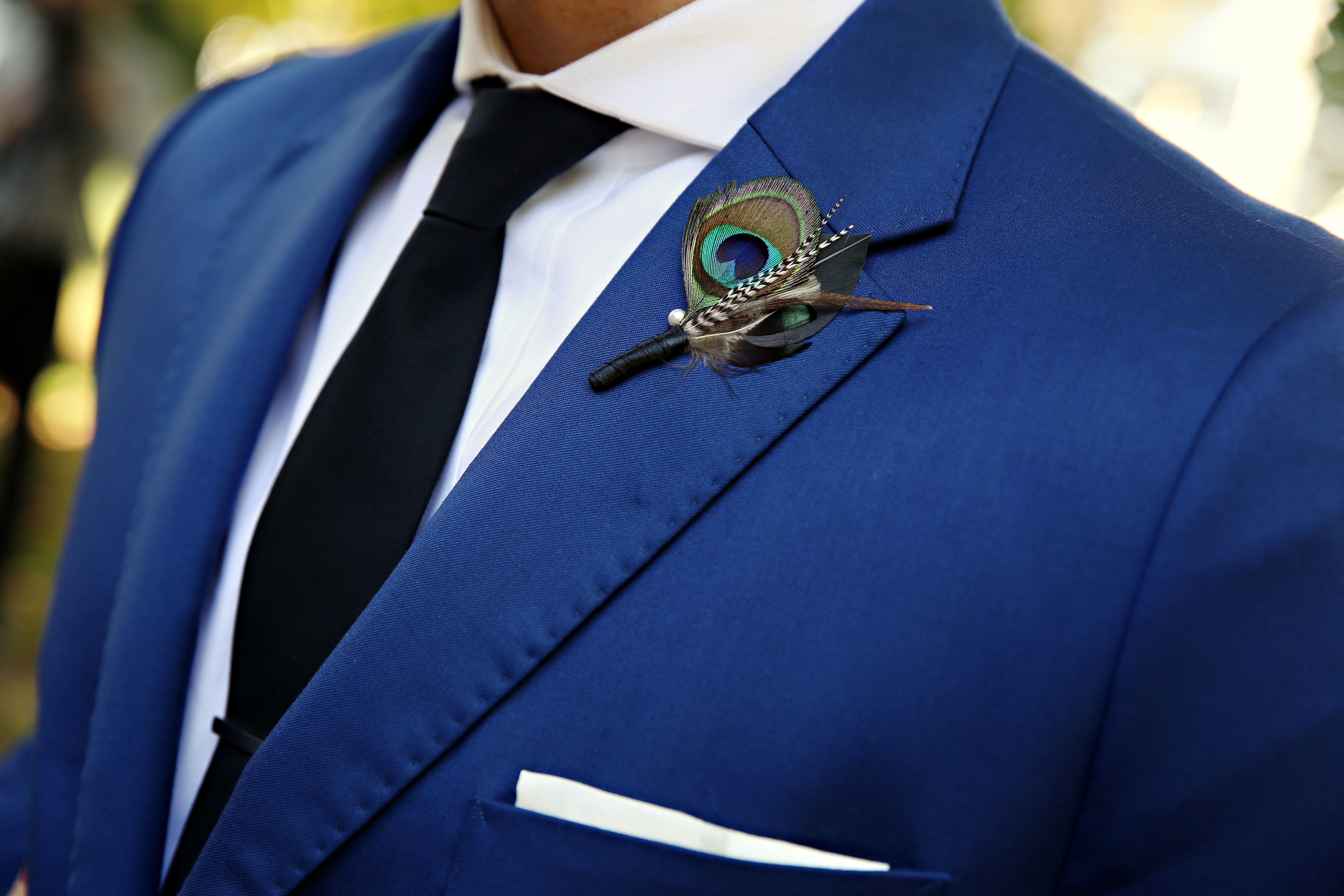 Groom In A Blue Suit With A Peacock Feather Boutonniere