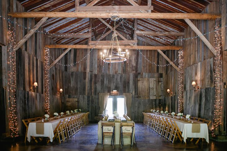 The exposed wood, rustic chandelier, drapery and string lights inside the Barn at Chestnut Springs  in Sevierville, Tennessee, made for a gorgeous reception spot. Katharine and Marc's guests sat at family-style dining tables and enjoyed a dinner of delicious Southern cuisine.