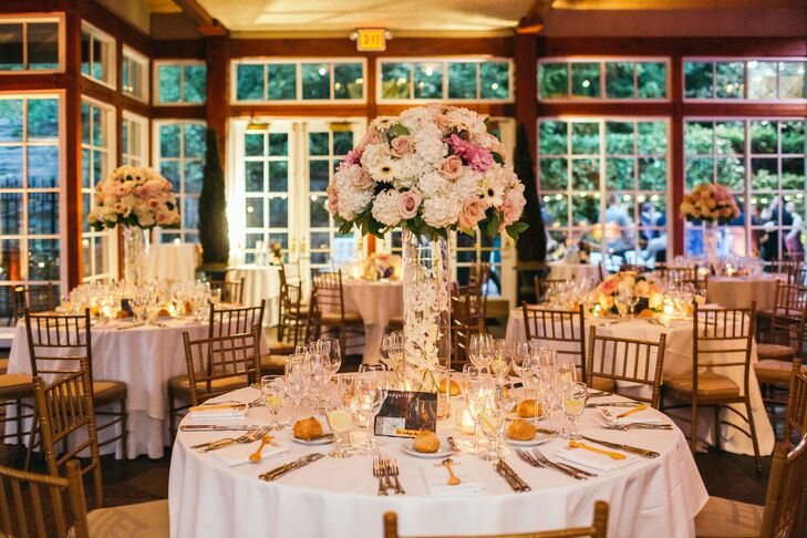 Michelle and Thorsten centerpieces consisted of white hydrangeas, quicksand roses,  touches of black-eyed gerbera daisies and cafe au lait dahlias. They were displayed in tall clear vases.