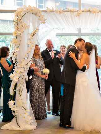 A whimsical white orchid and draped fabric wedding arch