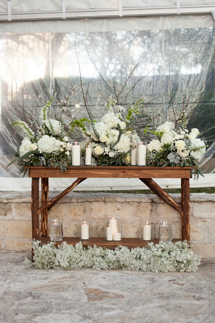 """My favorite decor piece was definitely the wooden altar Tyler hand-built for our ceremony,"" says Anne Elise. The florist then decorated the altar with a gorgeous collection of all-white flowers and candles."