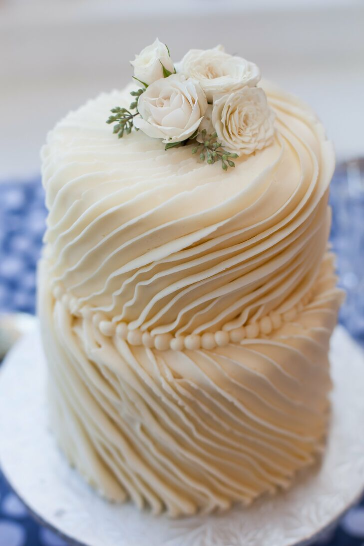 The wedding cake featured two round tiers with a ruffled pattern and piping between the tiers, topped with ivory garden roses.