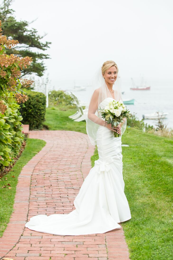 Classic elegance guided Alexandria's wedding dress decisions. She selected a strapless satin gown in a mermaid silhouette with a draped bodice, sweetheart neckline and bow-embellished skirt.
