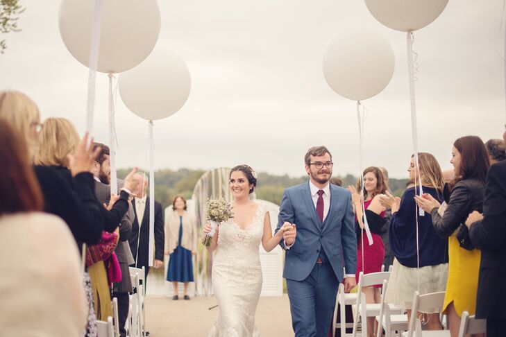 "After searching through Pinterest, Erin and Cory picked out a festive suit for his wedding day look.  He wore a ""postman"" blue suit and a burgundy tie with a subtle, matching blue pattern. His groomsmen, however,  stood out in navy blue suits and pale green ties."