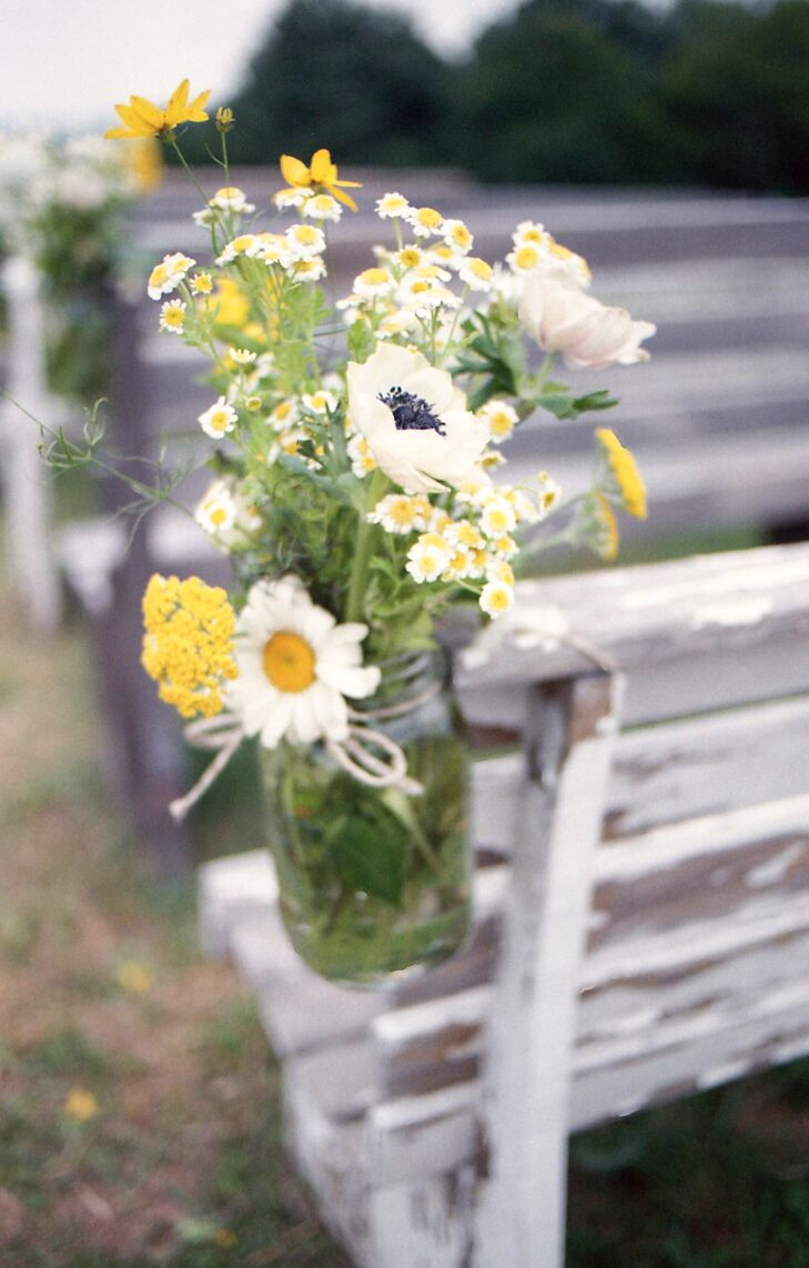 Yellow And White Flower Arrangements In Mason Jars As Aisle Decorations