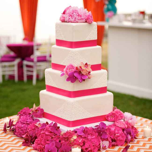 Four tiered cream and pink square wedding cake with hot pink flowers at base