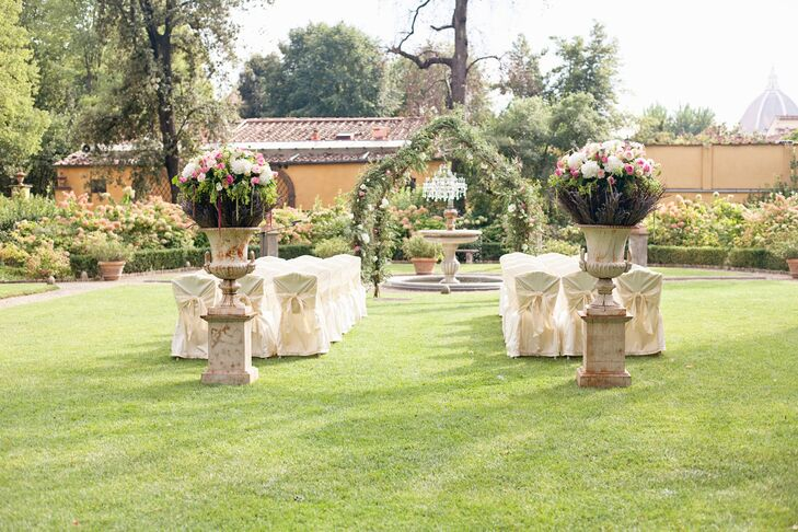 The ceremony took place in the garden at the Four Seasons Hotel Firenze in Firenze, Italy. The lawn overlooked the iconic Duomo. The wedding arch stood over the garden's fountain, and the ceremony aisle was marked by two large stone urns filled with white and pink flowers.