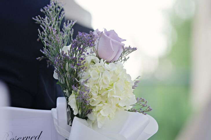 The ceremony aisle was lined with ivory hydrangeas and lavender roses tied to the white folding chairs with a white satin ribbon. The simple floral arrangements from Ray's Flower Shop added a little romance to the tented ceremony site. They also complemented the giant floral arrangements at the altar.