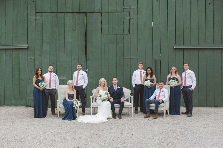 Christy, Brady and their wedding party posed in front of the green wooden building on the property. Bridesmaids wore strapless floor-length navy blue dresses while groomsmen wore bright coral ties, both complementing the color palette chosen for the day.