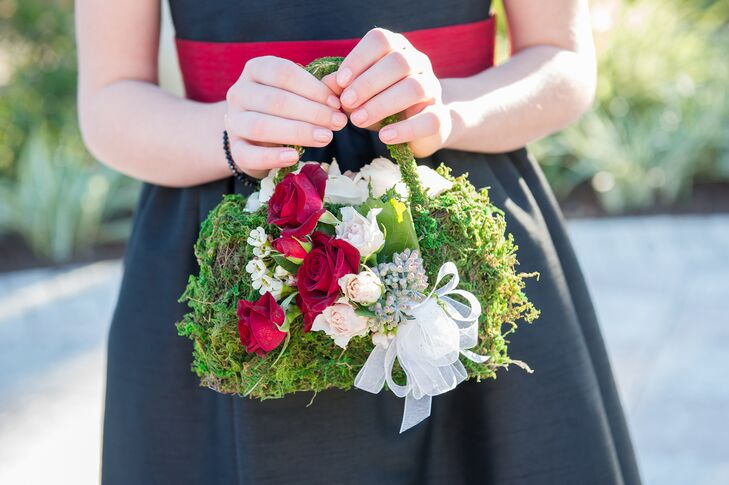 For a fun twist, the couple's flower girls carried red- and white-rose-accented moss purses filled with white flower petals down the aisle.