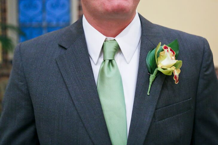 The groom wore a dark gray tuxedo with a green tie, and had a yellow lily pinned to the jacket.