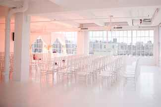 All white loft wedding ceremony space with white chairs