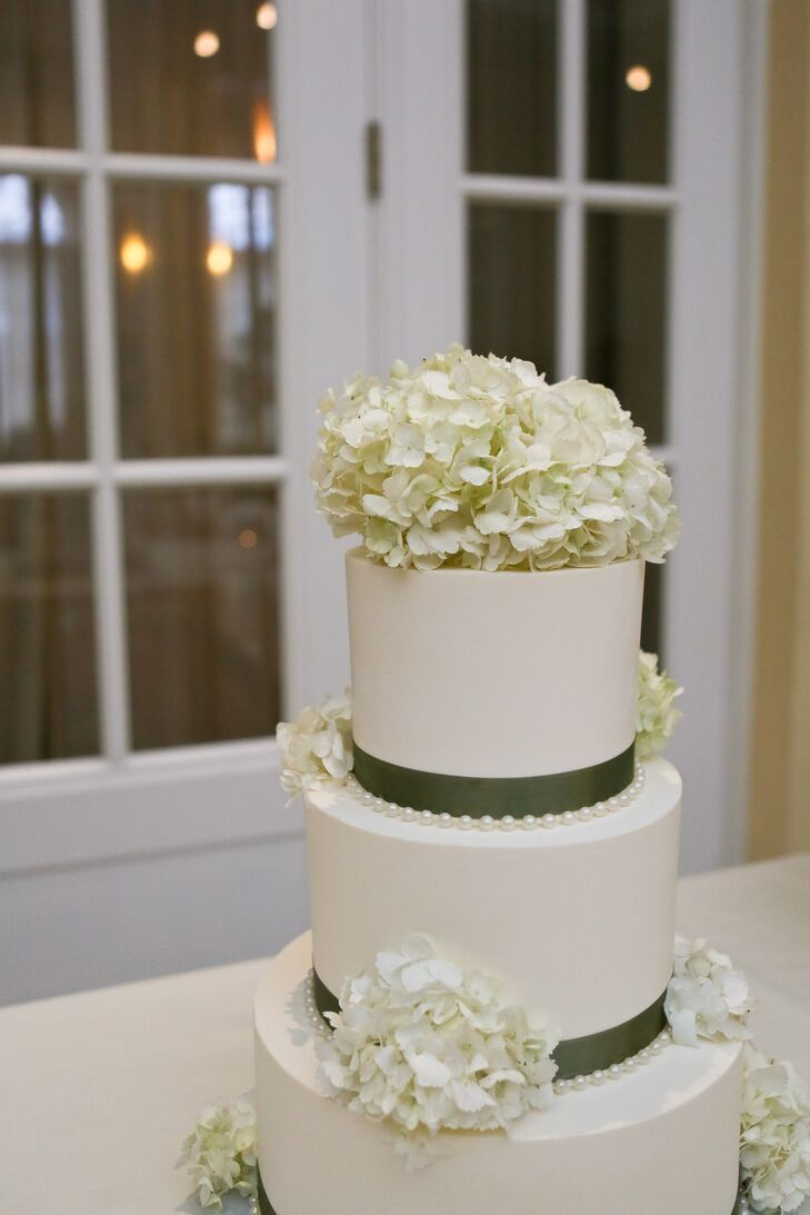 The ivory wedding cake had green ribbon wrapped around the base of each tier, and was accented with ivory hydrangeas.