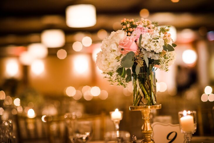 Lush arrangements of pink roses and white hydrangeas were placed on top of tall silver pedestals.