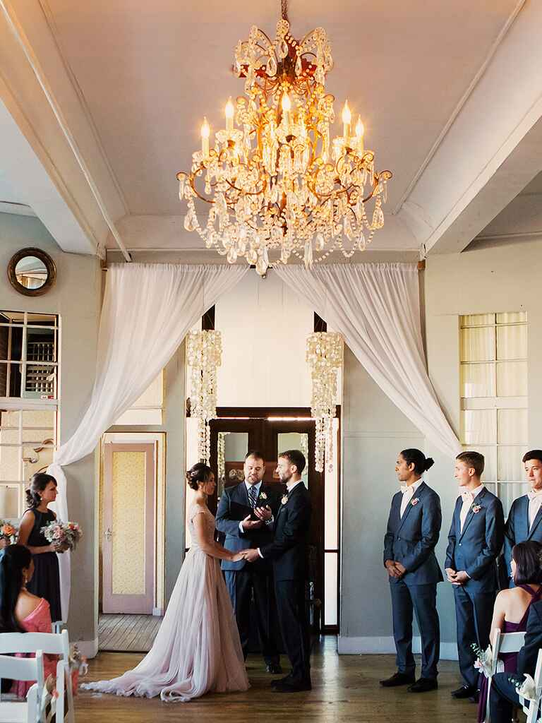 A stunning chandelier complimented by seashell wind chimes and a simple sheer fabric draped across the ceremony