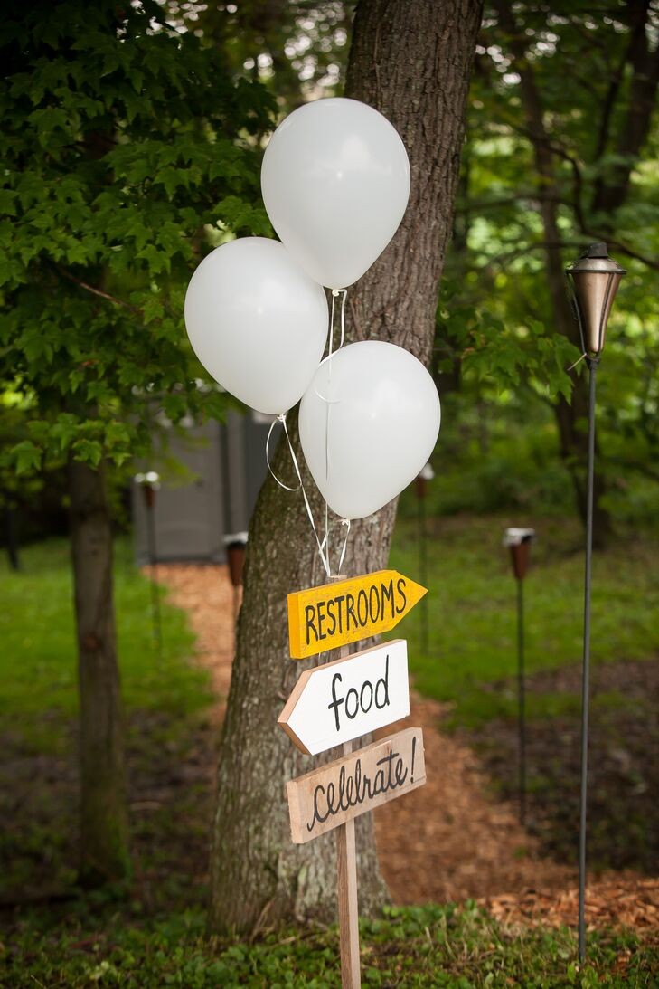 LeAnna and Matthew created rustic wooden signs decorated with white balloons to guide their guests around the tented reception.