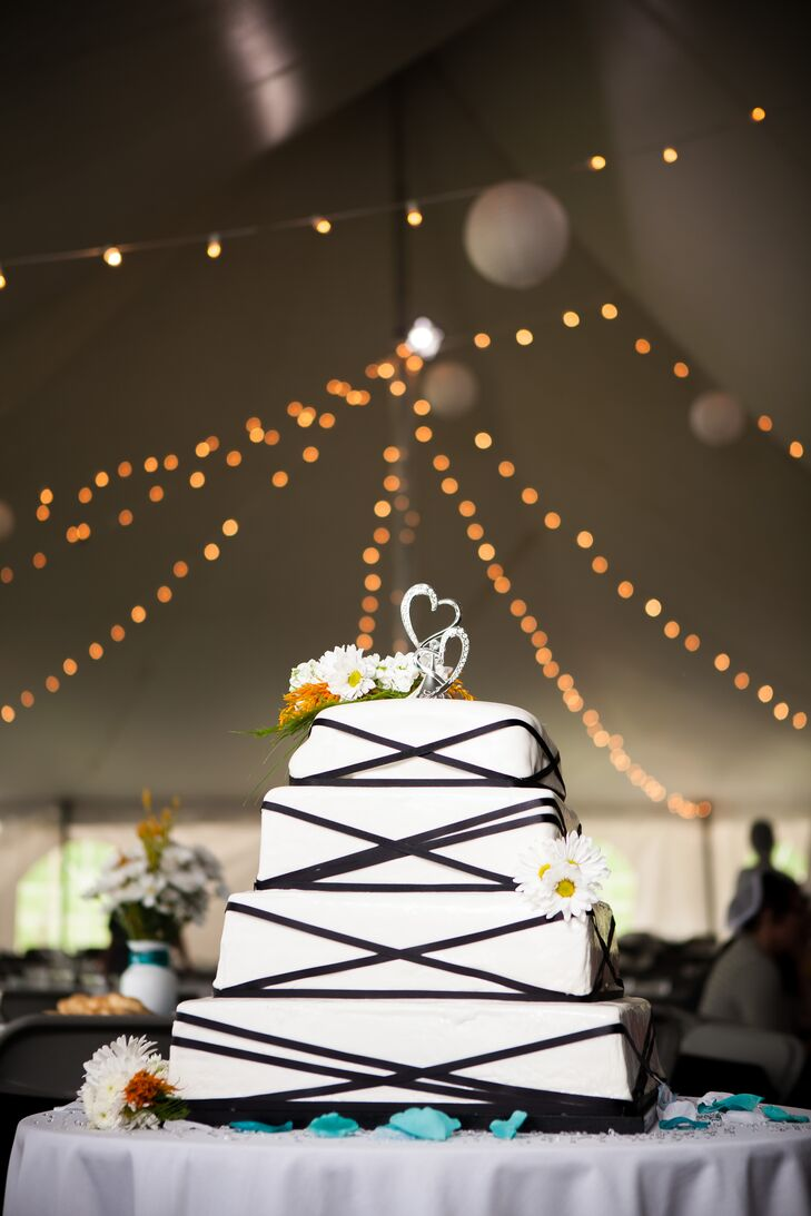 The tiered white wedding cake was decorated with daisies, black ribbon, and a sparkly heart cake topper. Guests could choose from either chocolate Ho-Ho cake or strawberry Bavarian cake served with a selection of ice cream.