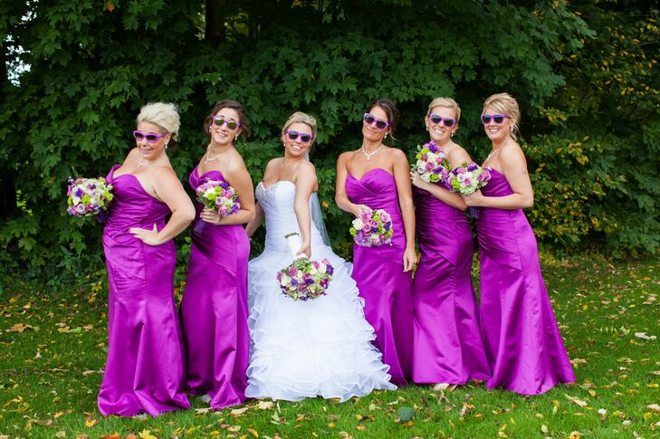 The bridesmaids wore strapless, purple satin, floor-length gowns to match the roses in their bouquets. They also wore matching updos and found purples sunglasses in the same shade as their dresses to wear for festive photos.