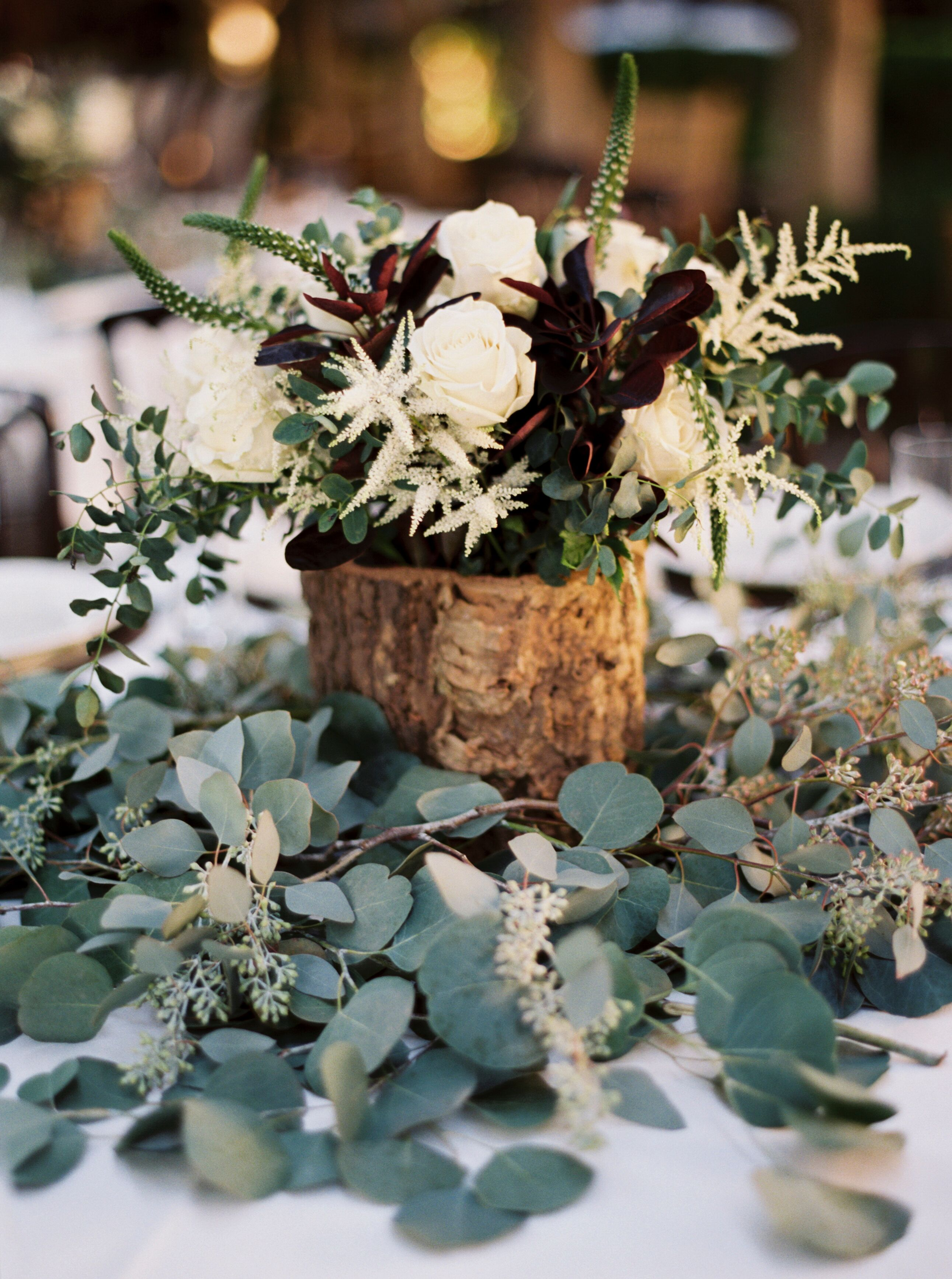 Rustic Wooden Centerpiece On Eucalyptus Leaves
