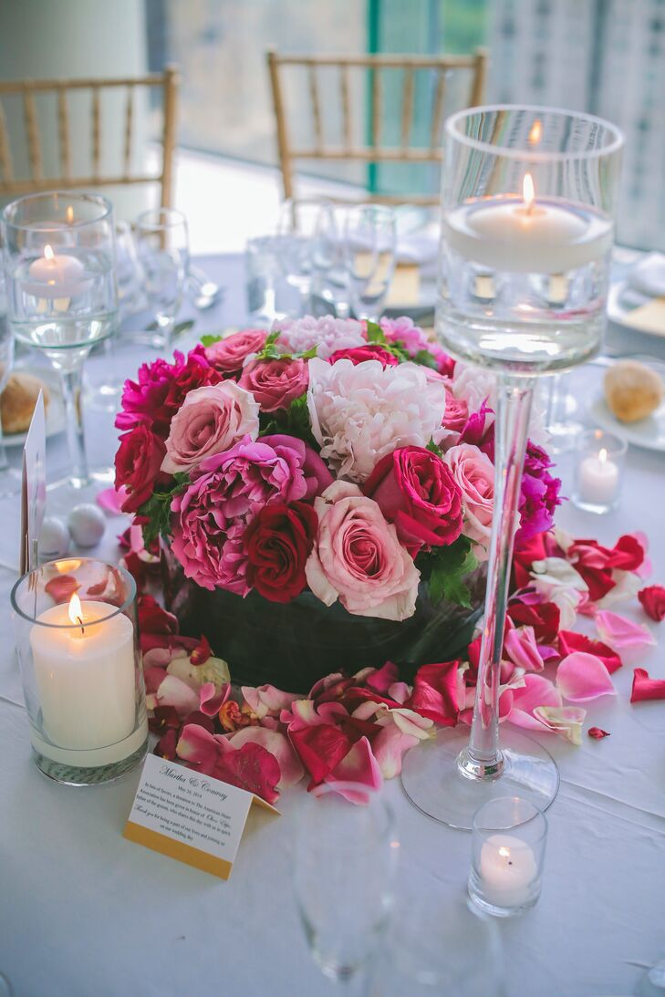 Reception centerpieces included tables with low, clear vases filled with pink peonies, roses and ranunculuses framed with thick rose petals.
