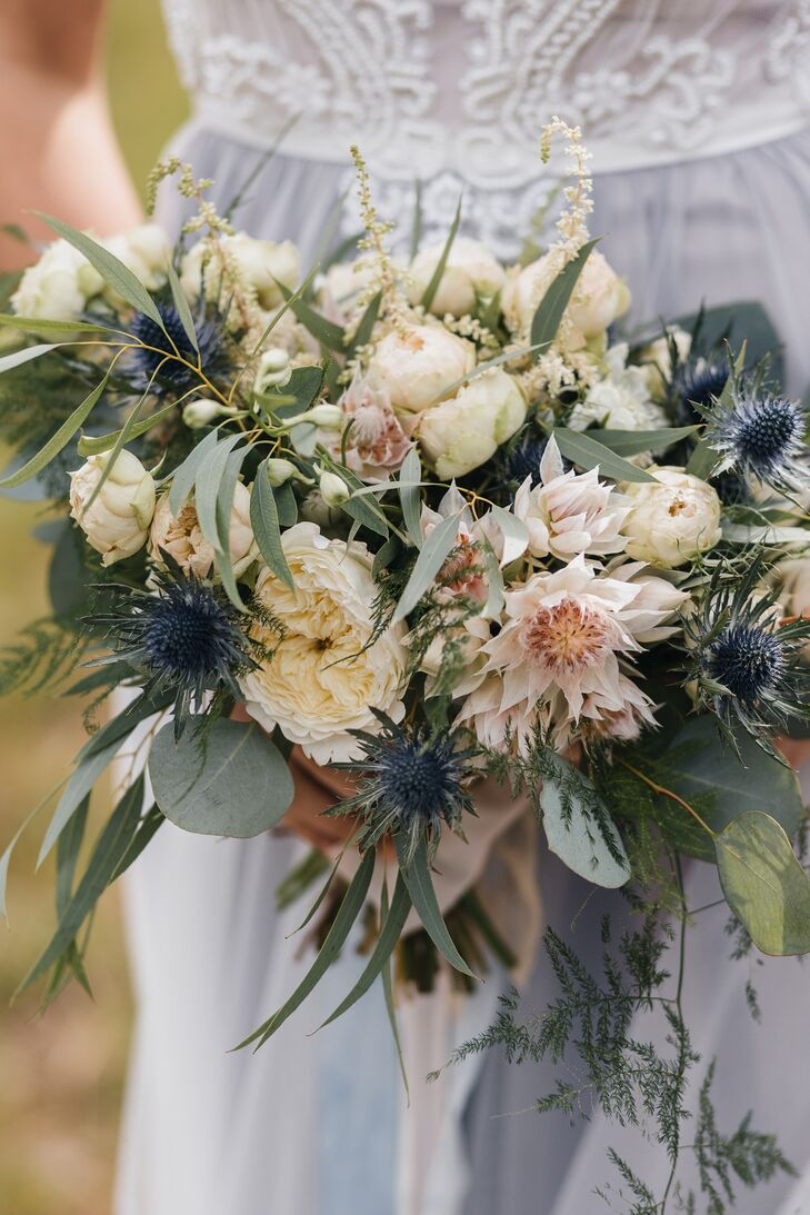 """I wanted my bouquet to be green with some pale colors and a little bit messy—in a good way—since my wedding look was simple but elegant,"" says Katya, who carried a bouquet filled with cream and blush blooms, greenery and blue thistle."