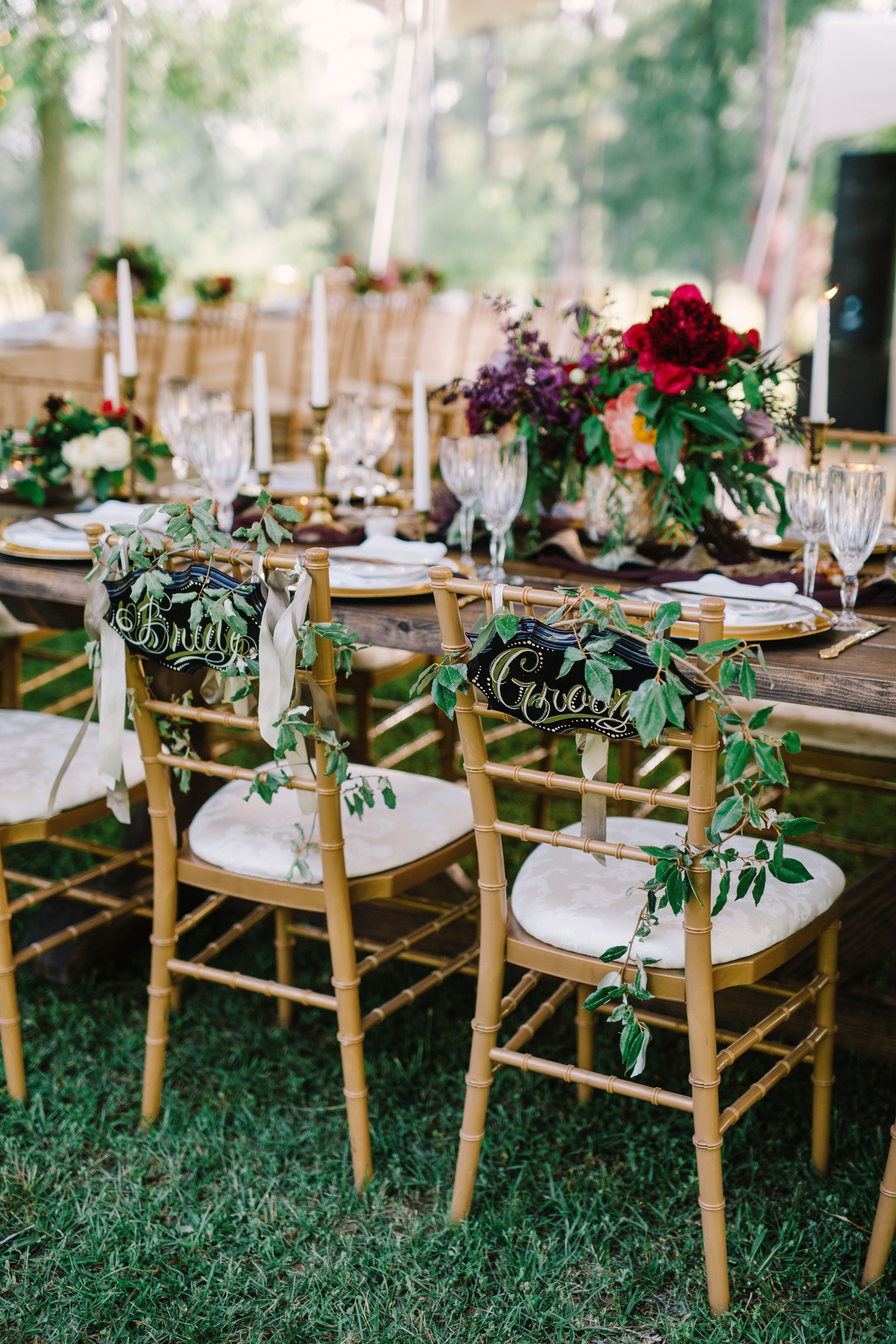 Gold Chiavari Chairs With Wild Greenery And Signs